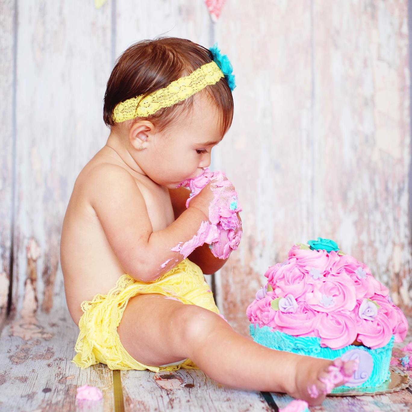 This adorable baby girl is smashing one of our giant cupcakes. The